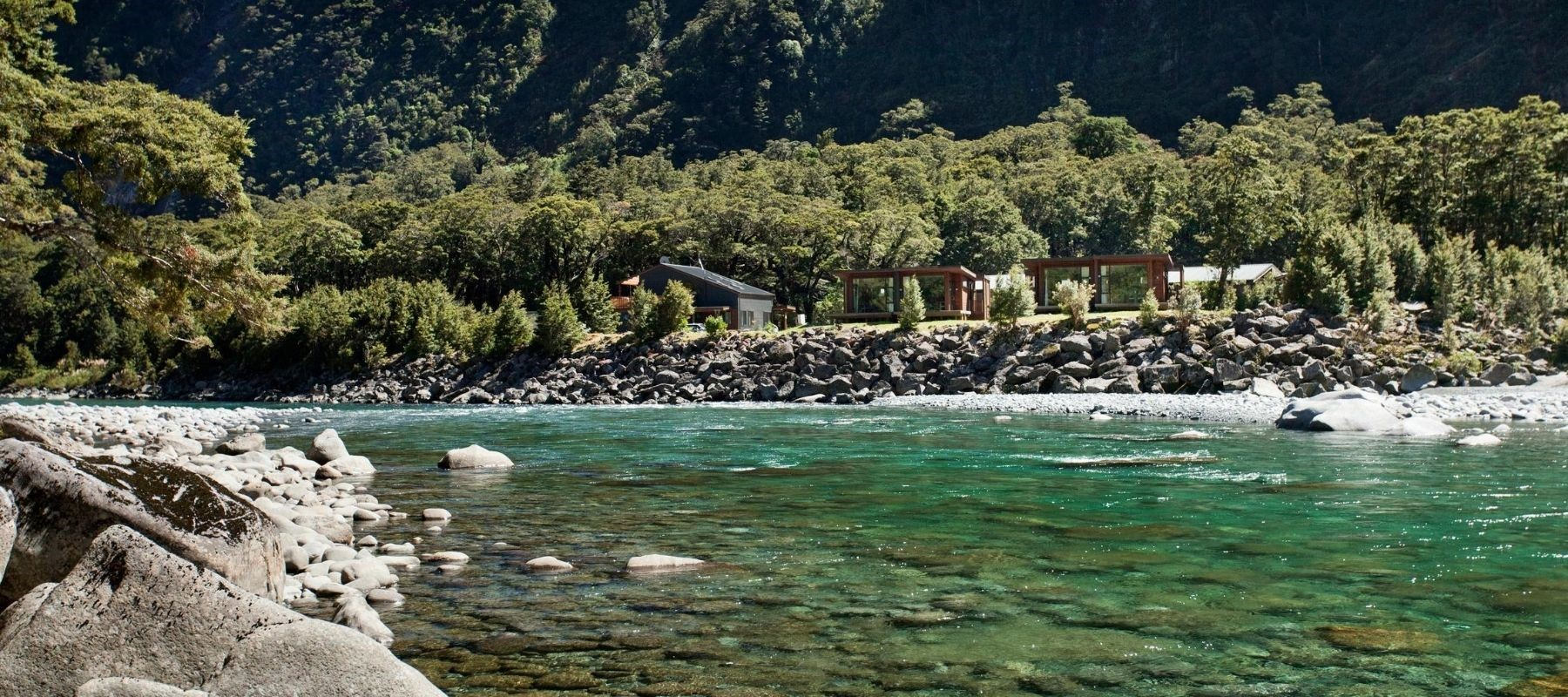 View of the flowing river with Milford Sound Lodge River Chalets in the background.
