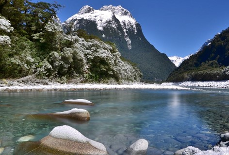 The clear blue river beside Milford Sound Lodge with snow settles on the tree, rocks and peaks.