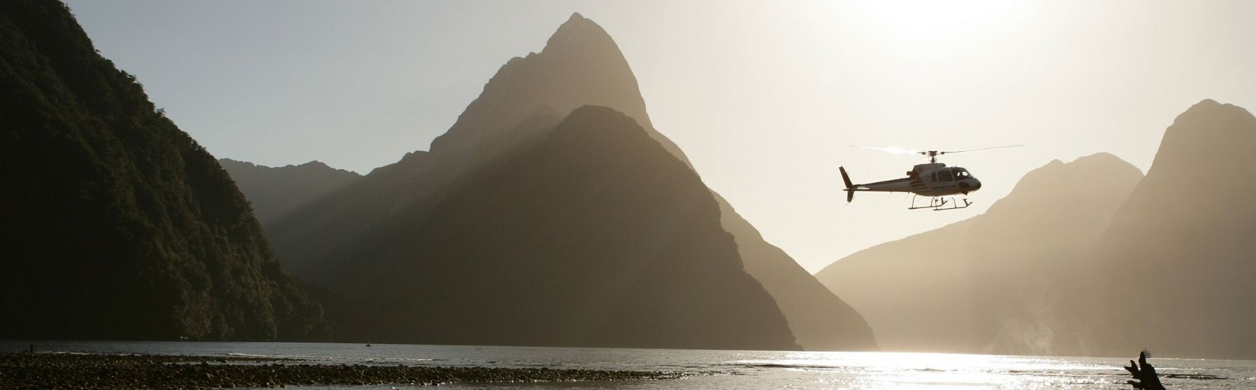 A helicopter flies above the Milford Sound near sunset between mountain peaks.