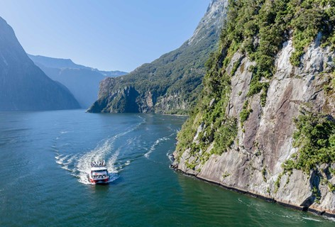 A Southern Discoveries boat churns water, taking tourists around the picturesque Milford Sounds.