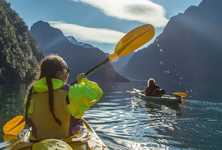 Three kayakers paddle through the Milford Sound on a sunny day from Milford Sound Lodge.