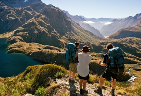 Three hikers look over the valley atop on the Routeburn Track, Milford Sound.