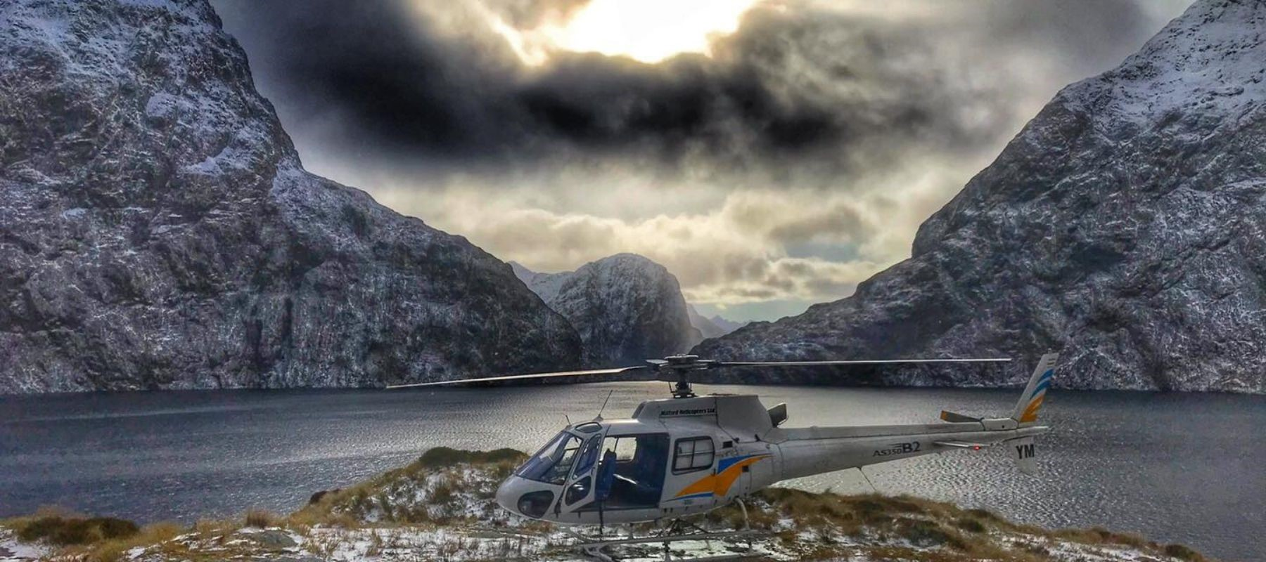 A helicopter sits on tussocks next Milford Sound from a scenic flight.