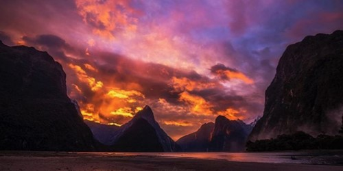 Sunset over the Milford Sound between the peaks, showing an incredible display of colour.