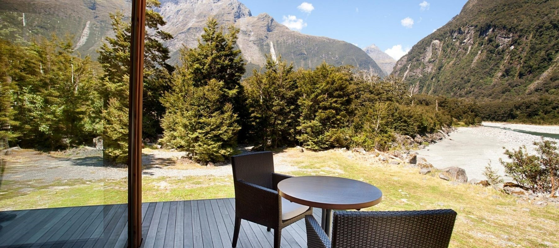 The deck at Milford Sound Lodge Riverside Chalet's with a table and chairs, looking over the river.