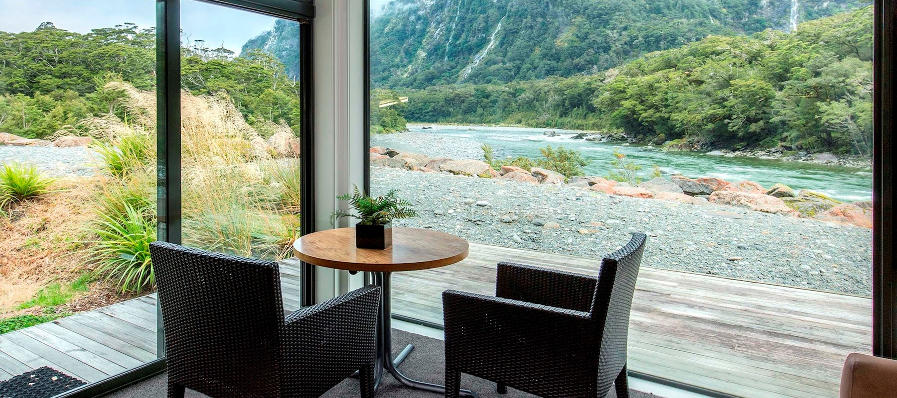 Floor to ceiling views over the from Milford Sound Lodge's Riverside Chalet's accommodation.