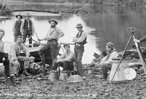 A black and white photo of gold miners sit riverside in Milford Sound.