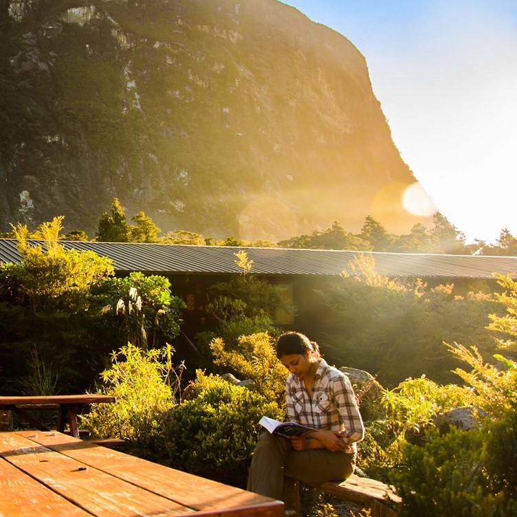A guest reads a book outside in the morning sunshine at Milford Sound Lodge.