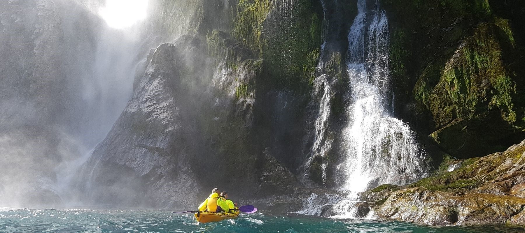 A double kayak heads towards a waterfall. One of the Milford Sound Lodge activities.