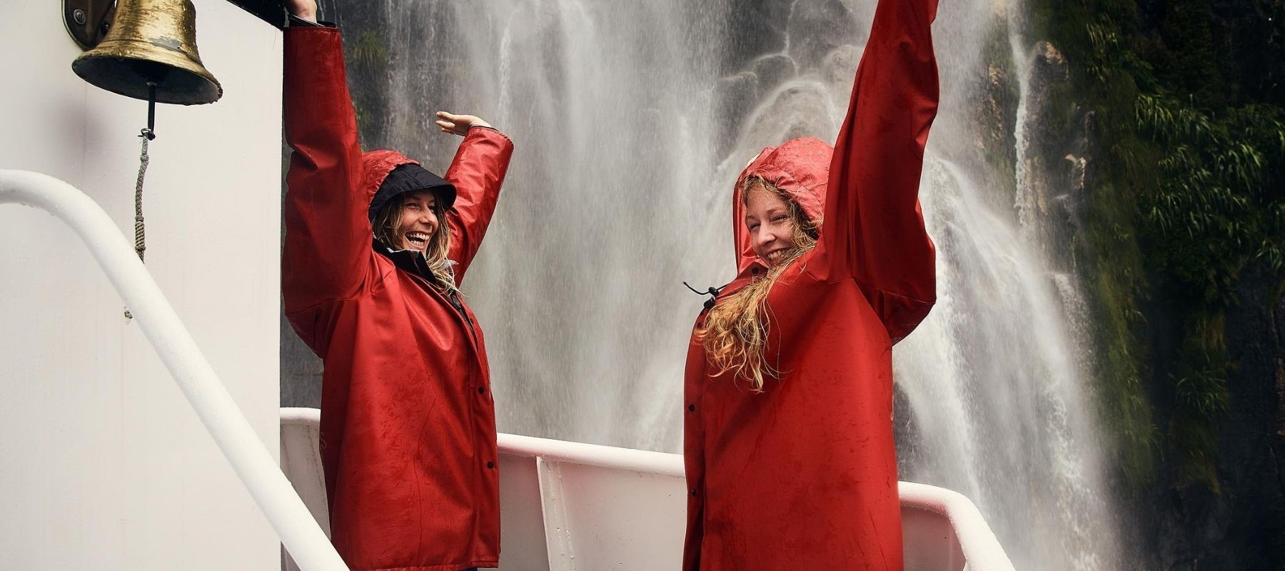 Two women enjoy waterfall spray from a Southern Discoveries boat tour from Milford Sound Lodge.