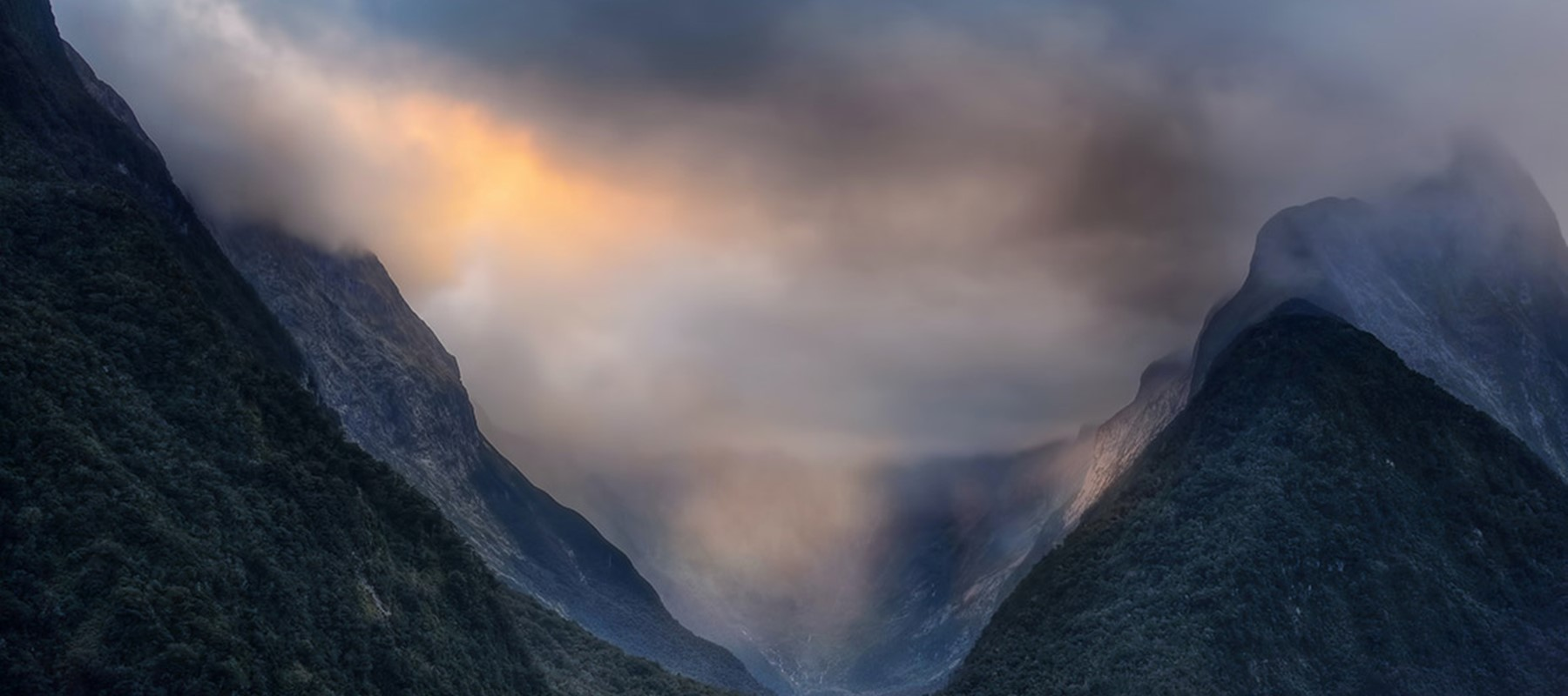 The sun breaks through grey clouds over Milford Sound between mountain peaks.