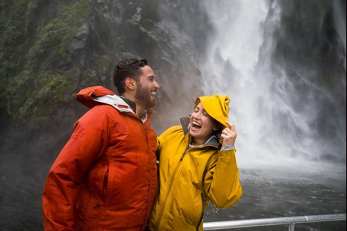 A couple laugh as they're splashed by a cascading waterfall on a Milford Sound Cruise.