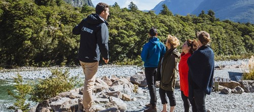 A Milford Sound Lodge tour guide explains the area's geography to a private tour group.