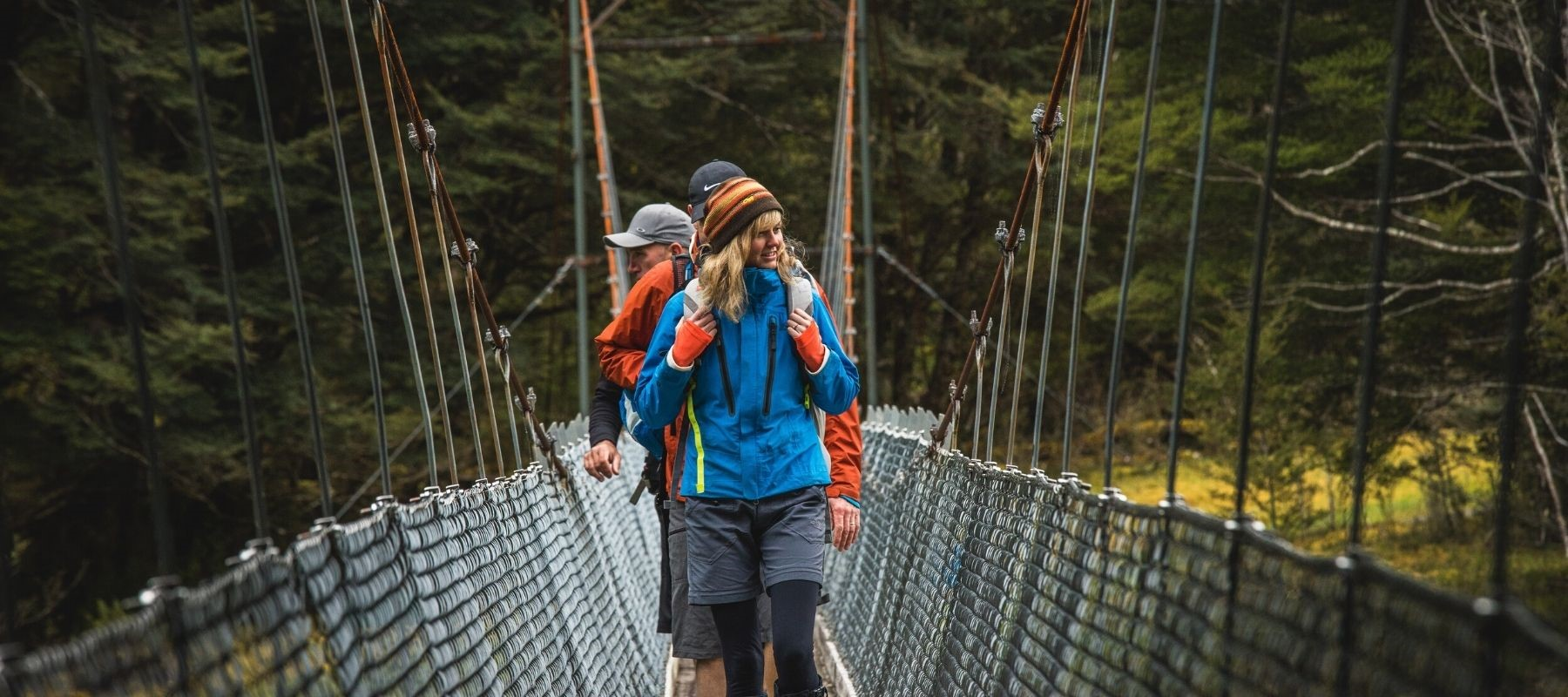 Three hikers stand on a bridge along the Milford Track.