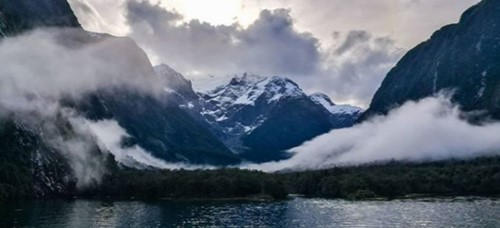 Low hanging clouds over Milford Sound with a dusting of snow on the peaks.