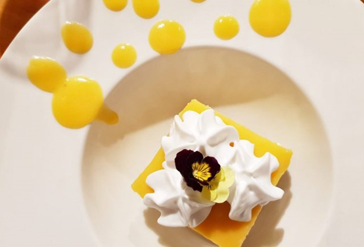 A lemon tart plated with cream and pansies at Milford Sound Lodge's Pio Pio Restaurant.