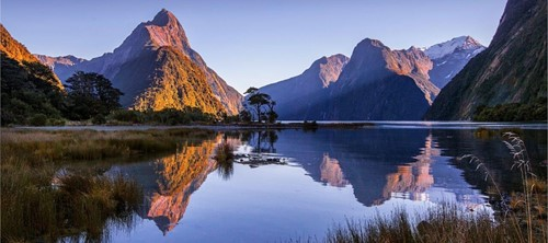 The morning sun aluminates peaks, perfectly mirrored in the calm Milford Sound.