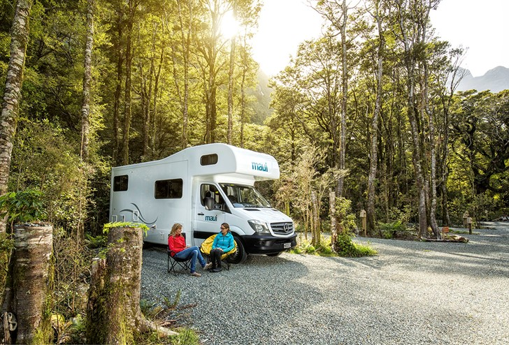 A couple sits outside their campervan at the Milford Sound Lodge Rainforest Campervan Park.
