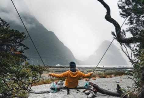 A child enjoys a swing on the banks for Milford Sound with mountain peaks in the background.
