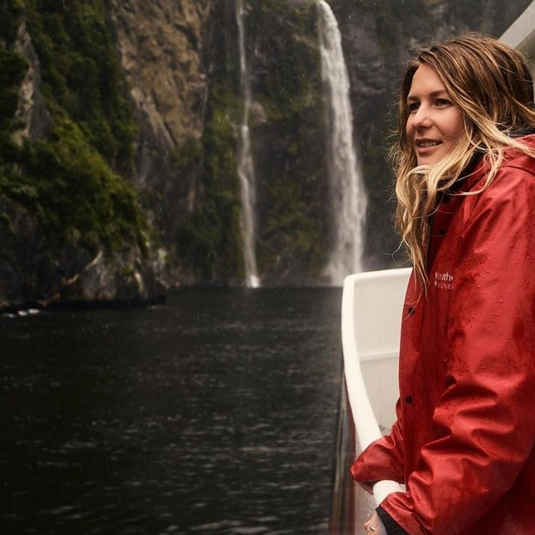 A young female enjoying a Milford Sound Cruise beside a waterfall.