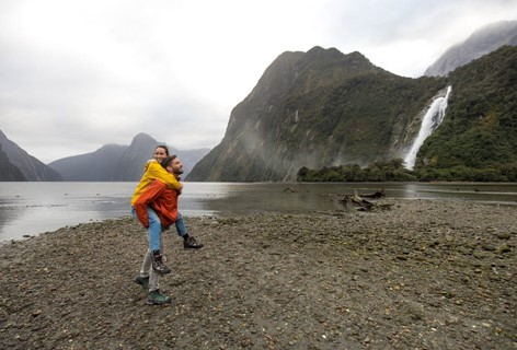 A couple walks along the stony Milford Sound shore with a waterfall in the background.
